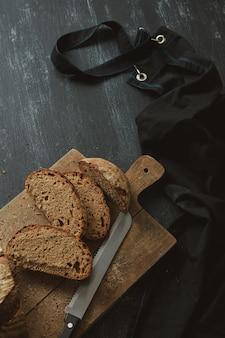 Frisches brot mit einem messer auf dem küchenbrett in scheiben schneiden