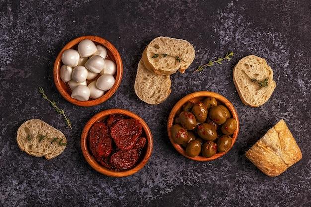 Frisches brot mit oliven, mozzarella und sonnengetrockneten tomaten