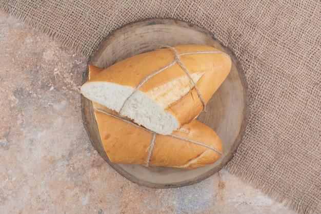 Frisches brot mit seil auf holzbrett gebunden