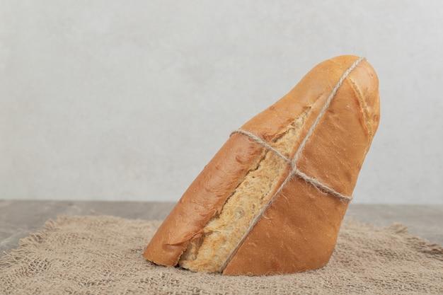 Frisches brot mit seil auf sackleinen gebunden. hochwertiges foto