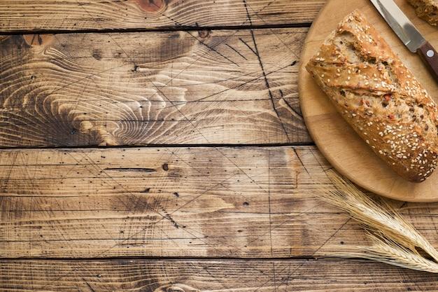 Frisches brot mit sonnenblumenkernen, sesam und flachs wird auf einem schneidebrett in stücke geschnitten. holztisch