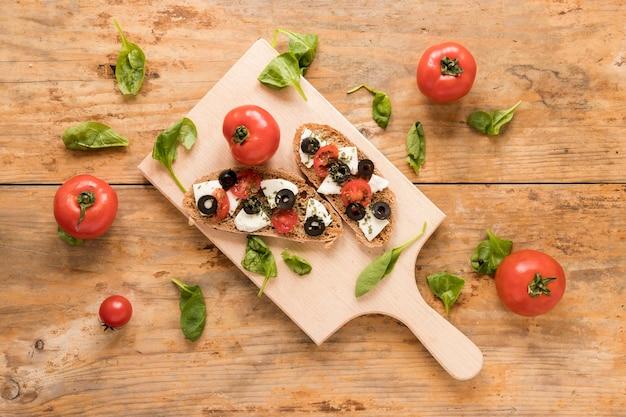 Frisches bruschetta auf dem hölzernen schneidebrett umgeben mit spinat und tomate