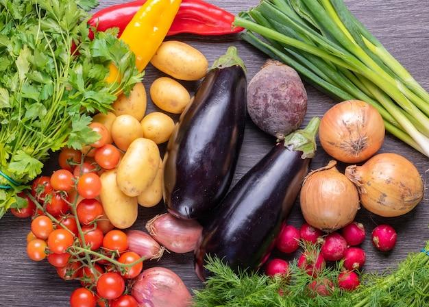 Frisches buntes bio-gemüse auf einem rustikalen holztischhintergrund, landwirtschaft und gesundes lebensmittelkonzept.