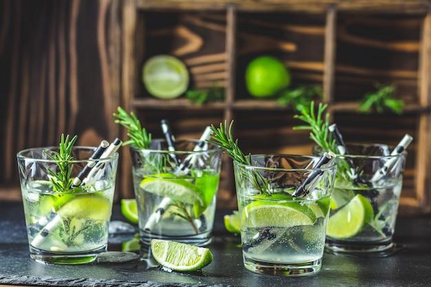 Frisches cocktail mit kalk, eis und rosmarin, mojito-cocktail in einem büro auf einer rustikalen tabelle