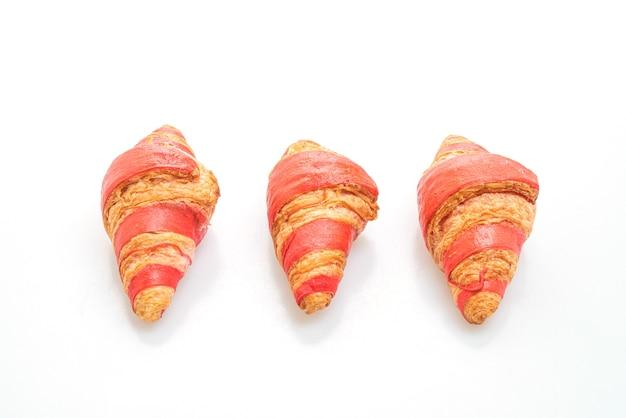 Frisches croissant mit erdbeermarmeladensauce lokalisiert auf weißer oberfläche