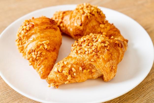 Frisches croissant mit erdnuss auf teller