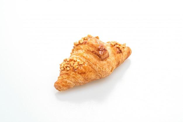 Frisches croissant mit erdnuss isoliert auf weißer oberfläche