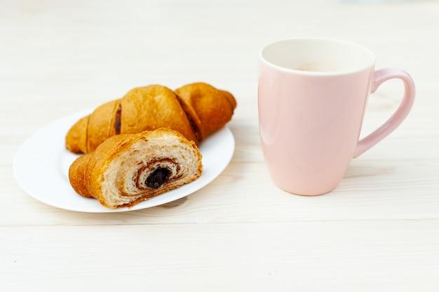 Frisches croissant mit schokolade auf dem weißen holztisch