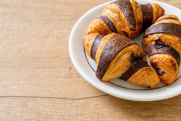 Frisches croissant mit schokolade auf teller