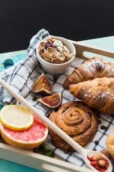Frisches croissant; süßes gebäck; cornflake; feigen- und zitrusfrüchte serviert zum frühstück im tablett