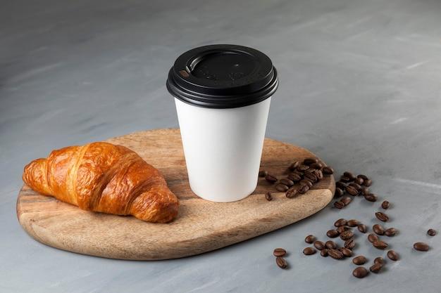 Frisches croissant und kaffee in einem weißen pappbecher auf einem hölzernen schneidebrett auf einem grauen hintergrund