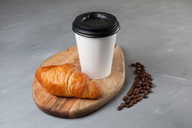 Frisches croissant und kaffee in einem weißen pappbecher auf einem hölzernen schneidebrett. in der nähe befinden sich mehrere kaffeebohnen.