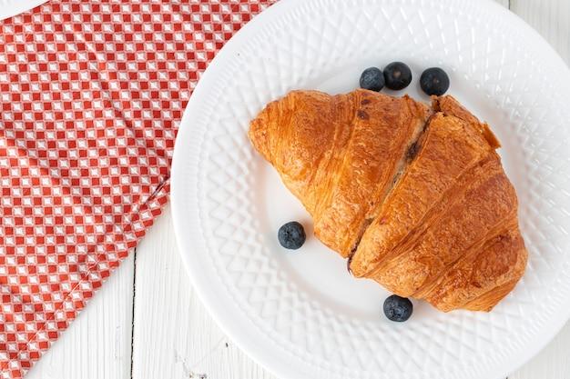 Frisches croissant verziert mit beeren auf weißem holzbrett, draufsicht