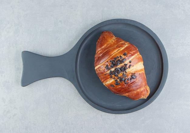 Frisches croissant verziert mit tropfenschokolade auf schwarzem brett.