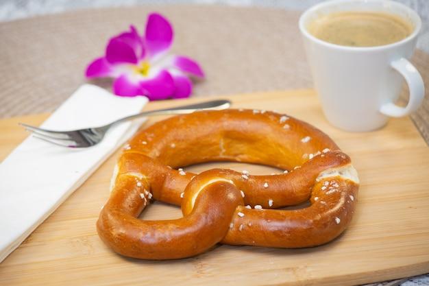 Frisches duftendes brot mit einer schönen blume und kaffee ist ein gutes frühstück für den körper auf dem tisch.