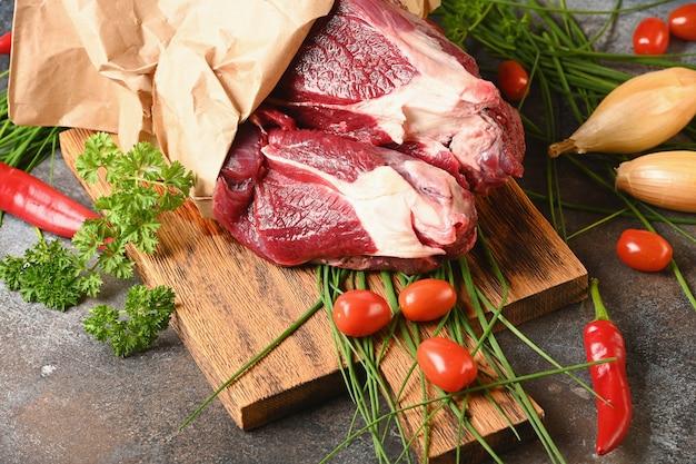 Frisches dunkles fleisch mit zutaten zum kochen auf braunem holz geschnitten