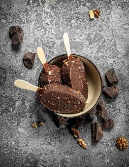 Frisches eis am stiel in schokolade mit nüssen. auf einem rustikalen hintergrund.