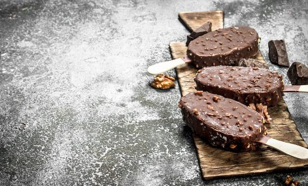 Frisches eis auf einem stock in der schokolade mit nüssen auf einem rustikalen hintergrund