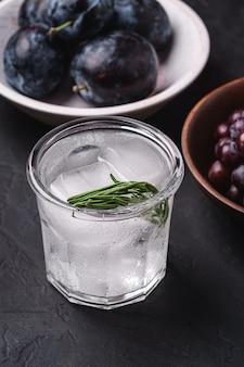 Frisches eiskaltes kohlensäurehaltiges wasser im glas mit rosmarinblatt nahe an holzschalen mit trauben- und pflaumenfrüchten, dunkle steinoberfläche, winkelansicht