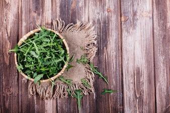 Frisches Essen, gesundes Leben. Grüner Arugula diente in der Schüssel auf rustikalem Hintergrund