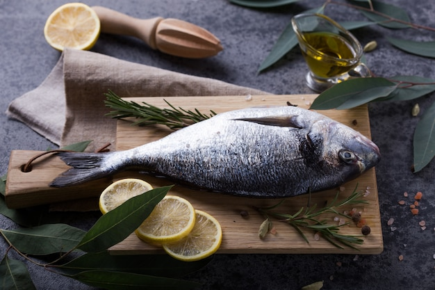 Frisches fischdorado auf schneidebrett auf grauem steintisch mit zutaten zum kochen. draufsicht mit kopierraum.