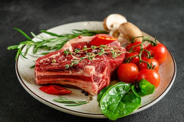 Frisches fleisch auf teller mit zutaten zum kochen