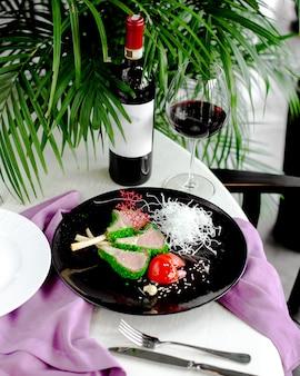 Frisches fleisch mit grüner sauce und tomate auf dem tisch