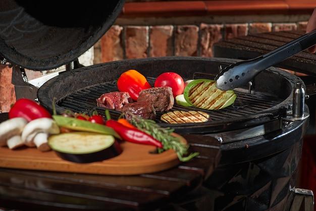 Frisches fleisch und gemüse, gegrillt bei einem hausgemachten wochenendgrill. kochkonzept, dunkle küche.