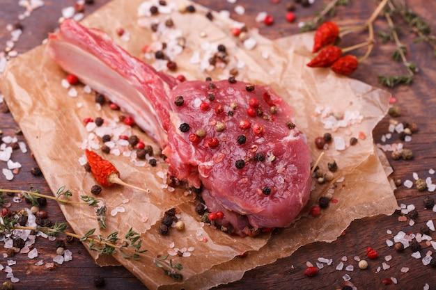 Frisches fleisch vom knochensteak mit gewürzen und kräutern