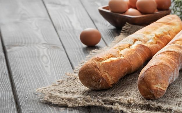 Frisches französisches baguette aus weißmehl neben hühnereiern und mehl