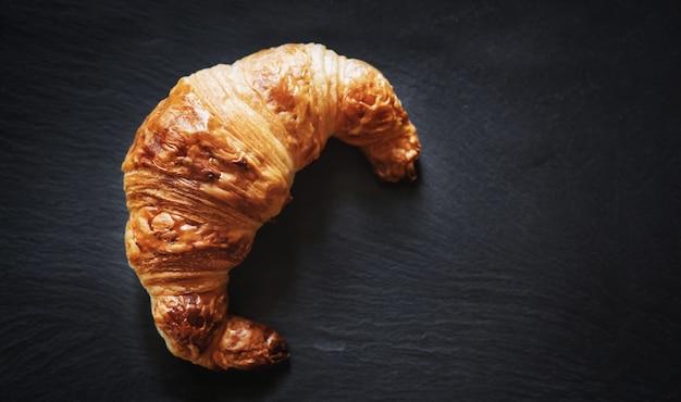 Frisches französisches croissant auf schwarzer steinteller-beschaffenheitstabelle