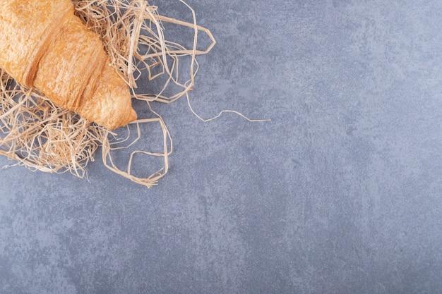 Frisches französisches croissant auf stroh über grauem hintergrund.