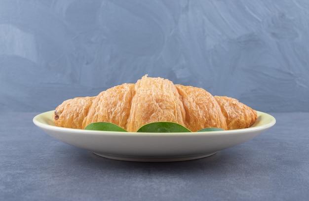 Frisches französisches croissant auf weißem teller über grauem hintergrund.