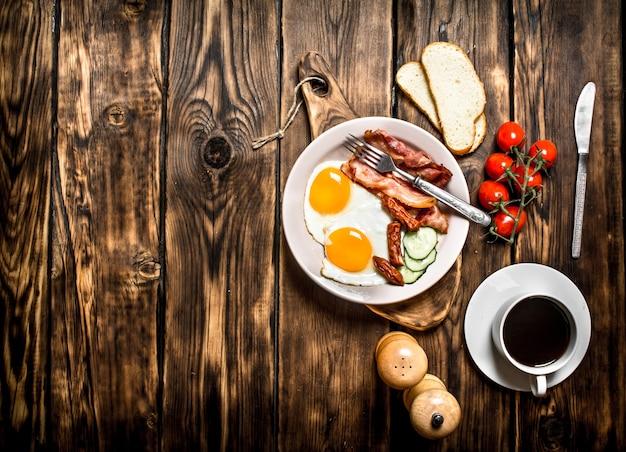 Frisches frühstück mit tasse kaffee, gebratenem beck mit eiern und tomaten auf einem holztisch