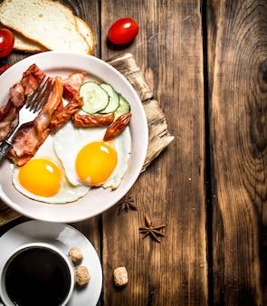 Frisches frühstück mit tasse kaffee, gebratenem speck mit eiern und tomaten auf einem holztisch