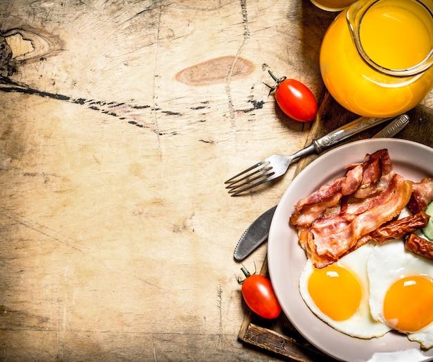 Frisches frühstück. orangensaft mit spiegeleiern, speck und brotscheiben. auf einem holztisch.
