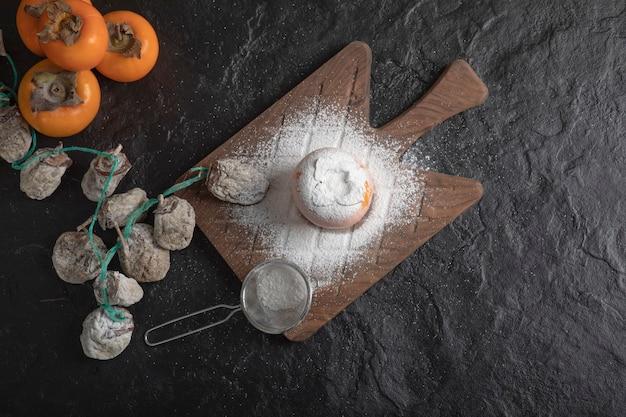 Frisches fuyu und getrocknete kakifrüchte auf schwarzer oberfläche