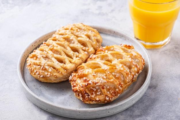 Frisches gebäck auf einem teller mit orangensaft. gesundes frühstückskonzept.
