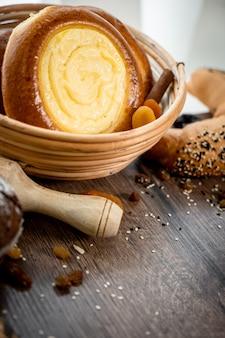 Frisches gebäck brötchen im korb in rustikaler bäckerei mit eiern und gluten auf holztisch