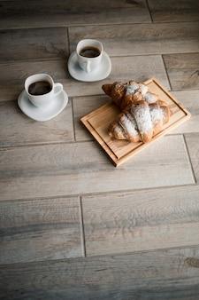 Frisches gebäck croissants mit schokolade auf einem holzbrett und zwei tassen schwarzen kaffee. romantisches frühstück