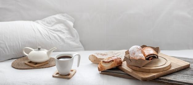 Frisches gebäck und eine tasse kaffee auf dem hintergrund eines weißen bettes. brunch- und wochenendkonzept.