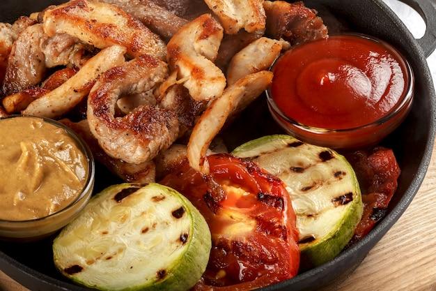 Frisches gebratenes fleisch mit gemüse, sauce und senf.