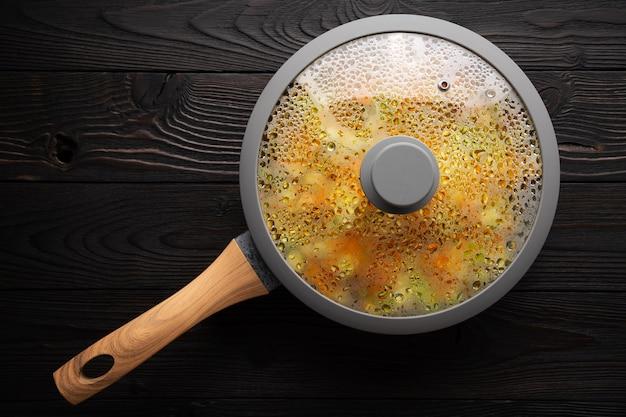 Frisches gedünstetes gemüse in einer pfanne auf hölzerner, flacher lage