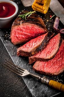 Frisches gegrilltes rindfleisch, hausgemachtes grillfleisch mittelrar, auf schwarzem steinschneidebrett, mit gewürzen