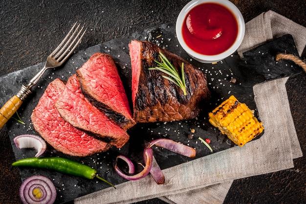 Frisches gegrilltes rindfleisch, hausgemachtes grillfleisch mittelrar, auf schwarzem steinschneidebrett