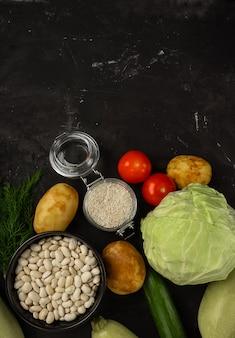 Frisches gemüse auf dem schwarzen hintergrund. gesundes lebensmittelkonzept