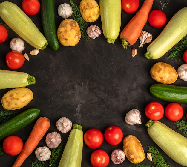 Frisches gemüse auf dem schwarzen hintergrund im flachen laienentwurf. veganes konzept