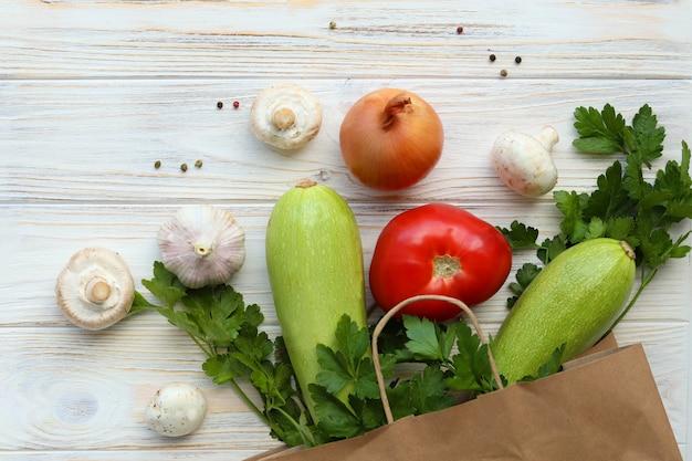 Frisches gemüse auf einem holztisch, gemüse in einer papier-öko-packung