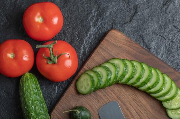 Frisches gemüse auf einem nassen schwarzen tisch geschnitten. tomaten- und gurkenscheiben auf holzbrett. hochwertiges foto