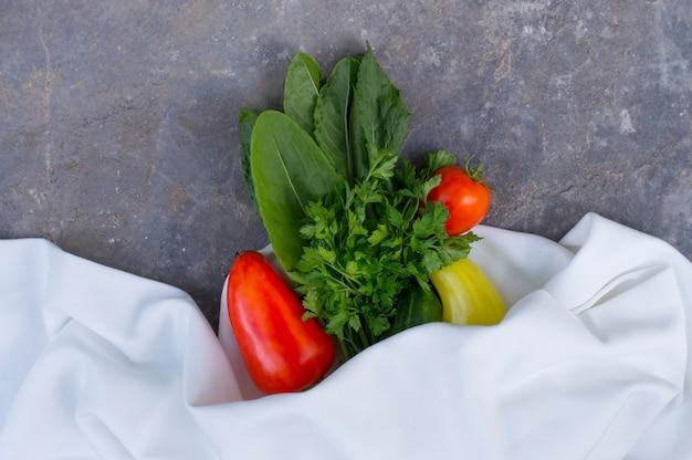 Frisches gemüse auf einem stein mit einem weißen tuch
